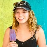 Teenage girl with braces eating a popsicle